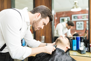 Focused Barber Trimming Client's Facial Hair In Salon