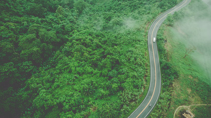 Aerial top view of sky road over top of mountain with fog and green jungle after raining in morning