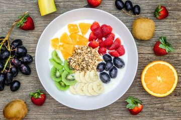 Plate of natural white yogurt with muesli, orange, banana, kiwi, strawberries and grapes fruits on wooden background. Yogurt and fruits as an ingredients around the plate. Top view. Healthy concept.