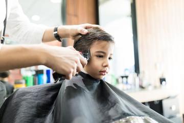 Boy Having His Hair Trimmed In Barber Shop