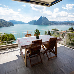 Large terrace overlooking the lake of Lugano on a summer day
