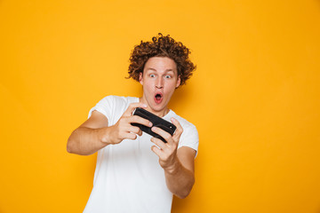 Young brunette guy in casual t-shirt playing online video games using mobile phone, isolated over yellow background