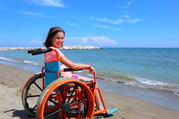 caucasian little girl on the wheelchair on the beach