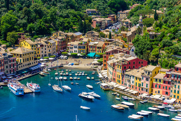 Portofino, Italy - colorful houses and yacht in little bay harbor. Liguria, Genoa province, Italy. Italian fishing village with beautiful sea coast landscape in summer season.