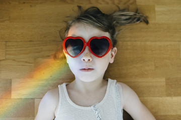 Overhead view of girl wearing heart shape sunglasses lying on hardwood floor at home