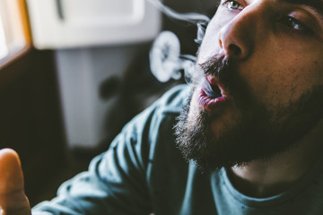 Close-up of bearded man exhaling smoke while smoking marijuana joint at home