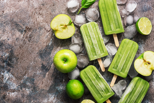 Green popsicles on a wooden background. Frozen juice on a stick, green apple, lime.Flat lay, top view.
