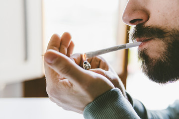 Midsection of bearded man igniting marijuana joint with cigarette lighter at home