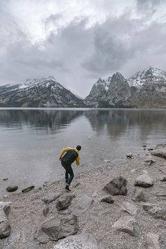 Full length of playful man throwing stone in lake against mountains and cloudy sky during winter at Grand Teton National Park