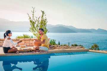 couple man and woman having breakfast by swimming pool during vacation in turkey