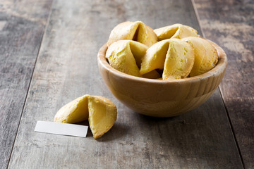 Fortune cookies in wooden bowl on wooden table