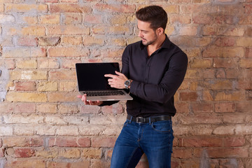 A serious handsome young businessman holding a laptop PC and pointing to the screen in a black shirt.