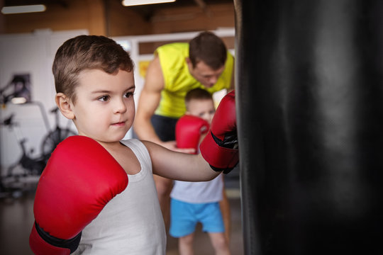 Little boy training with punchbag in boxing gym