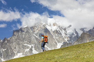 A trekker is walking in front of the Mont Blanc during the Mont Blanc hiking tours (Ferret Valley, Courmayeur, Aosta province, Aosta Valley, Italy, Europe).