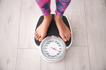 Woman measuring her weight using scales on floor, above view