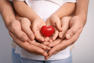 Family holding small red heart in hands together, closeup