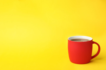 Red ceramic cup with hot aromatic coffee on color background