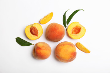 Composition with fresh sweet peaches on white background