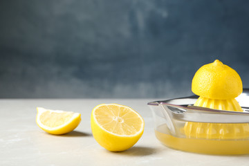 Slices of lemon and juicer on gray table
