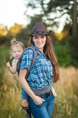 Cowgirl mother carrying her small daughter in a baby sling