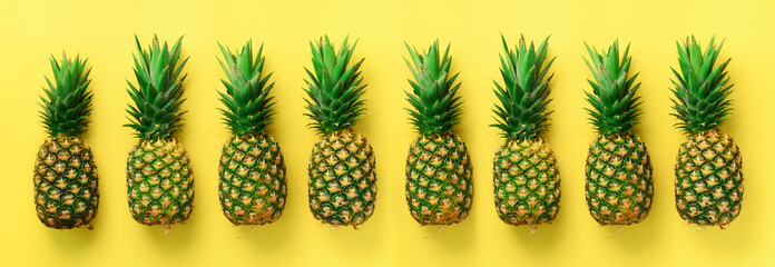Bright pineapple pattern for minimal style. Top View. Pop art design, creative concept. Copy Space. Banner. Fresh pineapples on yellow background.