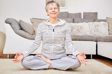 Seniorin im Lotossitz bei einer Yoga Übung