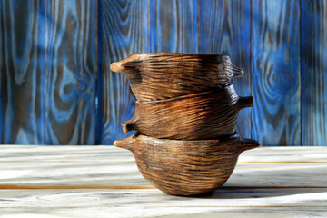 Stack of handmade ceramic bowls on rustic wooden table. Three empty stacked ceramic bowls