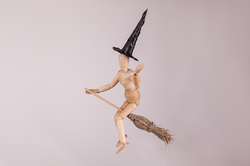 Halloween witch waving riding a witches broom wooden jointed dummy doll solid background