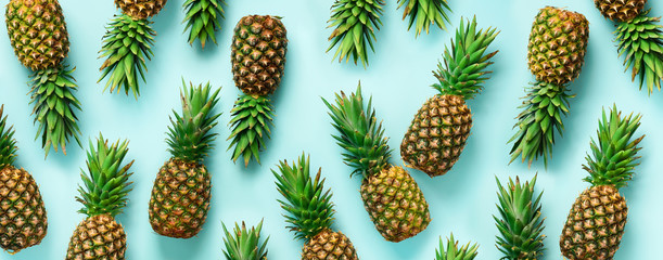 Bright pineapple pattern for minimal style. Top View. Pop art design, creative concept. Copy Space. Banner. Fresh pineapples on blue background.
