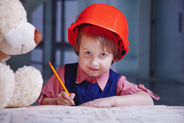 Cute little child girl architect in construction helmet planing and blueprints in office