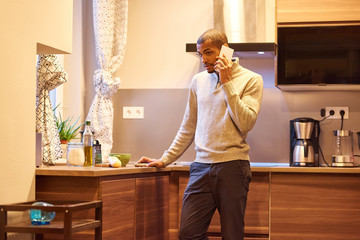 A serious handsome young man talking on his phone and cooking in the kitchen.