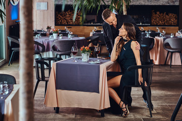 Elegantly dressed couple - handsome stylish male and charming brunette woman during the dating in a luxury restaurant.