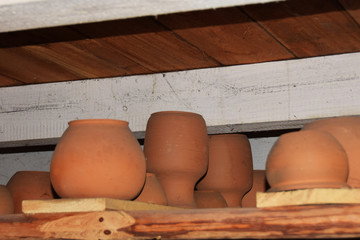 clay dishes made of clay in an old cottage in the Middle Ages are drying on a shelf under the ceiling