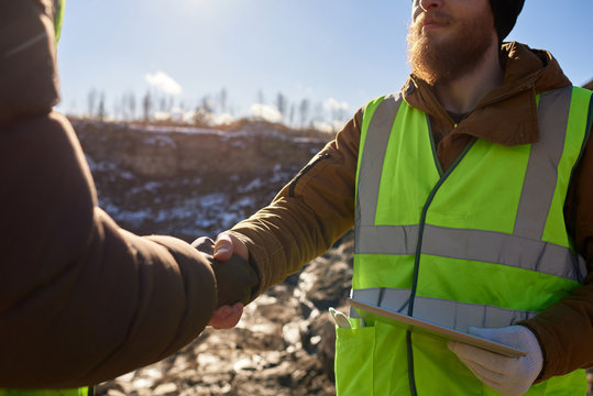 Mid section  portrait of bearded industrial worker wearing reflective jacket shaking with partner  outdoors