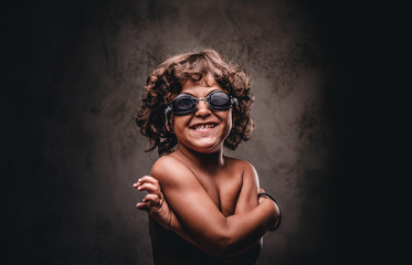 Happy little shirtless boy in swimming goggles posing in a studio. Isolated on the dark textured background.