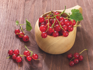 Fresh red currant in wooden mug on wood background