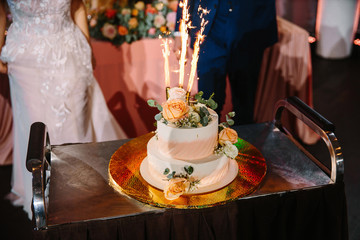 wedding cake at the wedding Banquet decorated with roses and other flowers