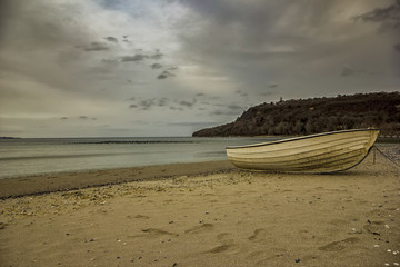 Fishing boat bow at the end of a day on sea beach background with copy space