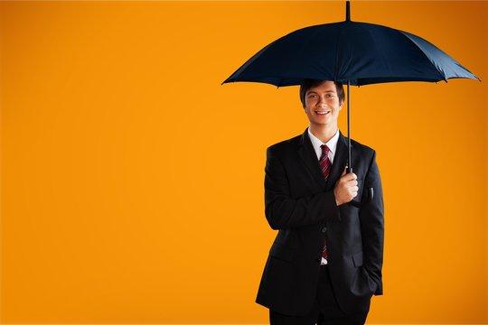 Businessman with umbrella on background