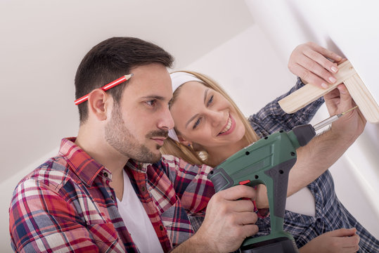 Young couple mounting wood shelf and doing repair at home together