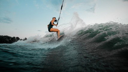 Young beautiful woman riding on the wakesurf holding a rope of a motorboat