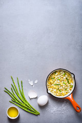 Healthy breakfast. Pan of fried scrumbled eggs with asparagus on grey background