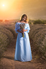 Brunette young woman in a blue dress with a bouquet of lavender in a lavender field during sunset