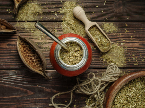 Mate yerba tea in calabash on wooden table. Traditional argentinian beverage
