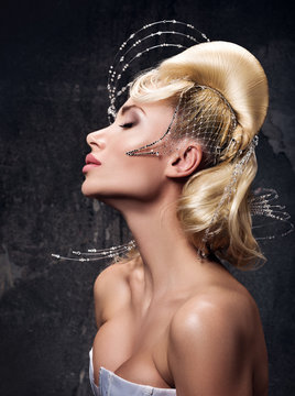 Vertical portrait of a beautiful young woman hair in the avant-garde style. A complex wavy form of the hair styling with the decor and rhinestones
