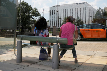 Two women wait for a bus across the street from the Embassy of Russia in Washington