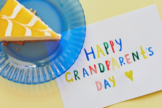 Happy National Grandparents day. Colored greeting card made by children and piece of cake on blue plate as gift