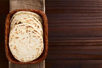 Homemade leavened Indian Naan flatbread in basket, photographed overhead on dark wood