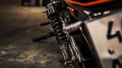 Close up view on rear shock absorber for a motorcycle. Chrome on moto parts. Wallpaper. Copy space. Rear view