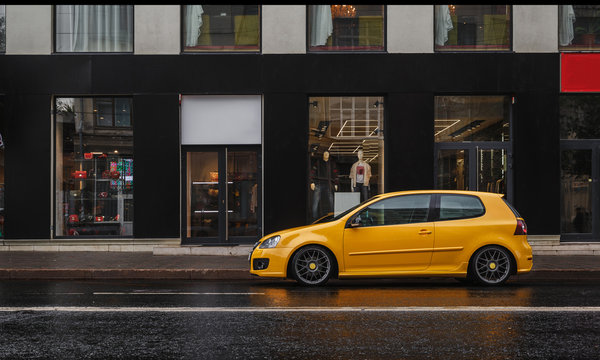 Yellow car is parked at asphalt road in the city center in the rain. Storefront